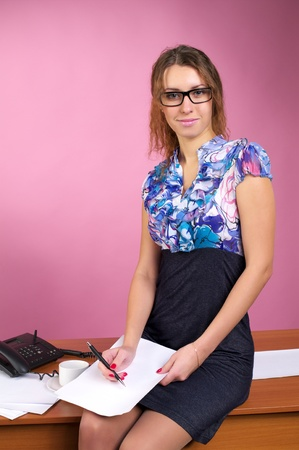 Attractive business woman sits on the table in the pink office photo
