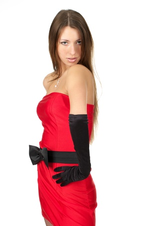 Cute young female in red dress looking over her shoulder over white background photo