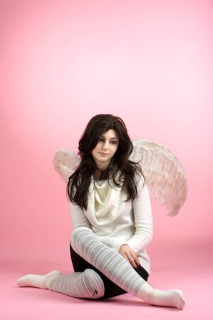 Sad angel sitting on the floor against pink background photo