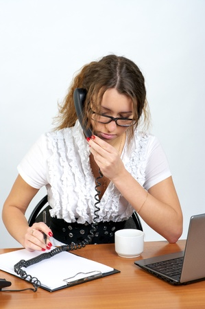 Cute business woman talking phone and writing something in the office photo