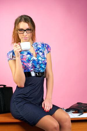 Attractive business woman sits on the table and drinks coffee photo