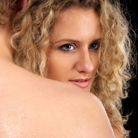 Beautiful naked woman looking over naked man shoulder photo