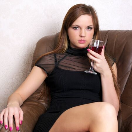 Beautiful woman drinking red wine sitting on a leather sofa Stock Photo - 8572714