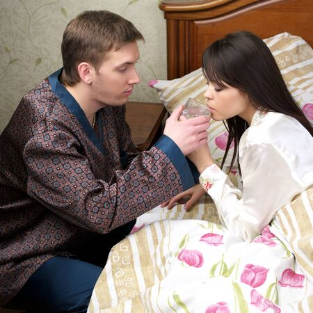 Attentive man give fresh water to sick woman at the bed photo