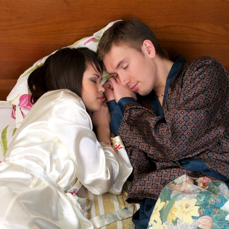 Young couple sleeping in the bed, face to face Stock Photo - 8600377
