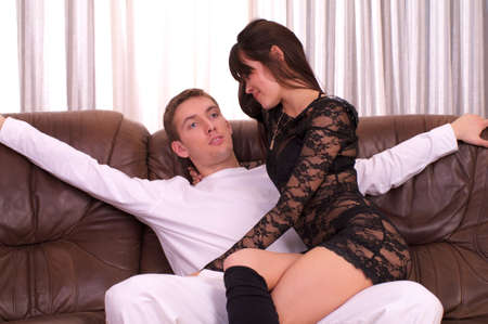 Man and beautiful woman sitting on leather sofa photo