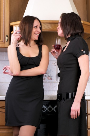 Two young beautiful women talking about something in the home kitchen with wine glasses photo