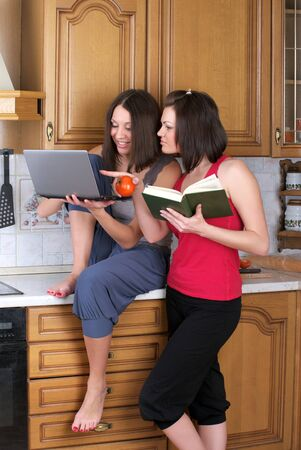 Two beautiful women searching receipt in the INTERNET photo