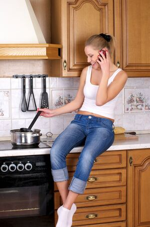 Young attractive woman cooks soup while talking phone photo