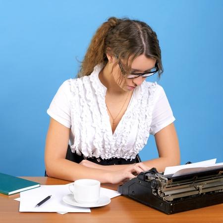 Cute female author with vintage typewriter writing something Stok Fotoğraf