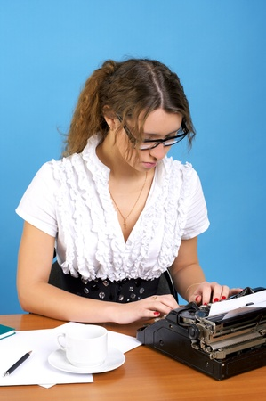 Cute female author with vintage typewriter writing something photo