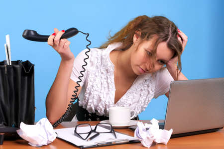 Overworked businesswoman holding telephone handset with unanswered call