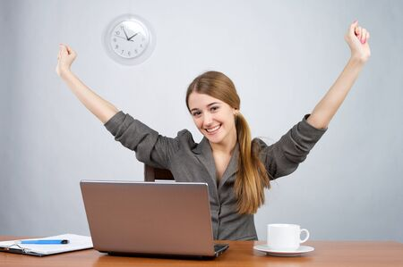 Businesswoman at desk with arms thrown up, while looking at camera Stok Fotoğraf