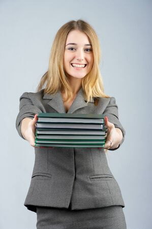 Beautiful business woman holding books and smiling