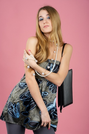Portrait of a beautiful sensual woman with handbag against pink background photo