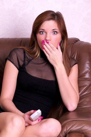 Portrait of surprised young woman with tv remote control in hand. Stock Photo - 9207000