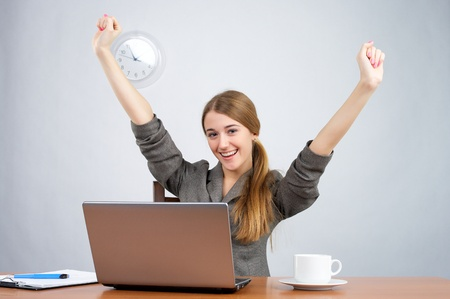 Businesswoman at desk with arms thrown up, while looking at camera Stock Photo