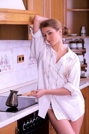 Beautiful young woman make coffee in domestic kitchen photo