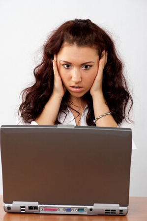 Portrait of beautiful young business woman at her desk, looking surprised to the laptop screen Stock Photo