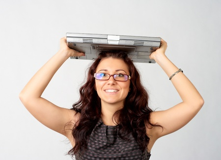 Portrait of young woman holding a laptop above her head photo