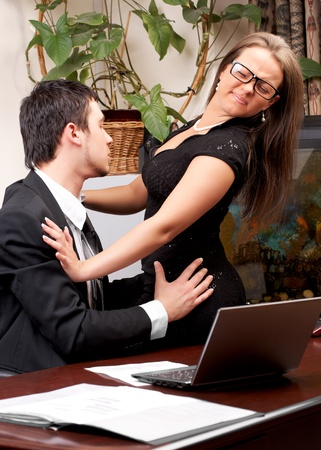 sexual: Young business man sexually harassing woman in office Stock Photo