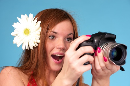 Beautiful young female photographer with white flower in hair photo