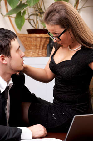 Businesswoman and businessman looking to each other eyes (in office) photo