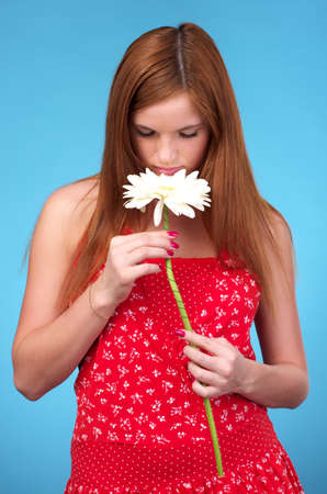 sundress: Pretty young woman in red sun-dress sniffing white flower