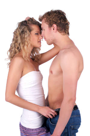 Beautiful young semi-dressed couple in love over white background Stock Photo