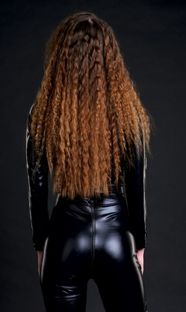 Rear view of woman in skintight latex with long curly hairs