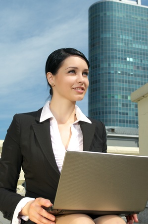 Beautiful business woman with laptop on the lap working outdoor