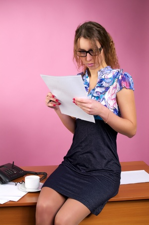 Attractive business woman sits on the desk in the pink office photo
