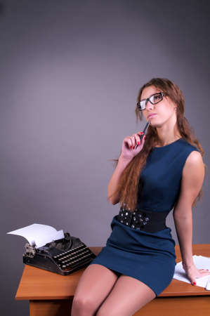 Cute pensive female author with vintage typewriter photo
