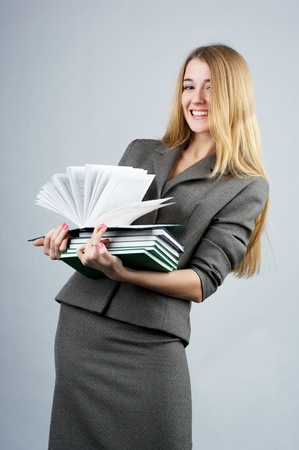 business attire teacher: Portrait of a beautiful cheerful businesswoman with books