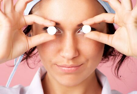 Closeup portrait of young nurse showing pills over eyes photo