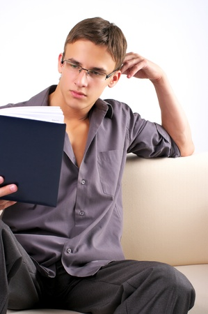 Young man reading book on the sofa at home photo