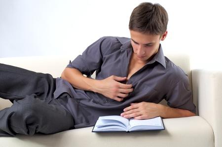 beau jeune homme: Jeune homme lisant un livre sur le canapé à la maison