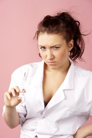 Young female doctor holding syringe photo