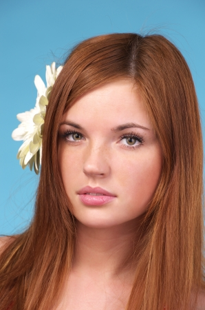 Closeup portrait of beautiful young woman with flower in hair