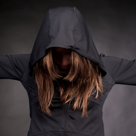 Closeup portrait of young woman in hood with hidden face