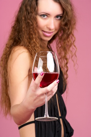 Cute young woman with glass of red wine, selective focus photo