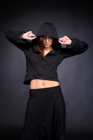 Beautiful young woman in hip hop style with hood on the head against black wall Stock Photo