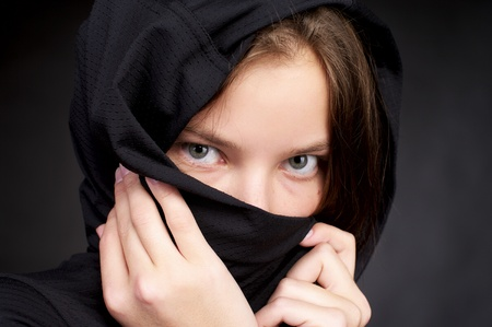 purdah: Beautiful woman hiding her face by black headscarf Stock Photo