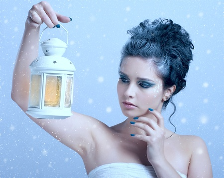 Closeup portrait of beautiful woman with winter style makeup and lantern in hand photo