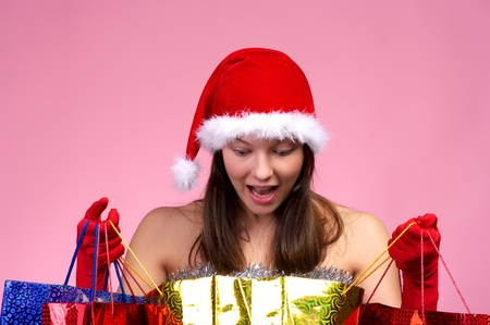 Happy beautiful woman in Christmas hat looking into shopping bag photo