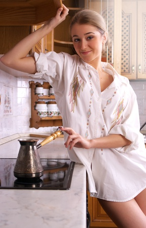 Beautiful sexy woman make coffee at home kitchen photo