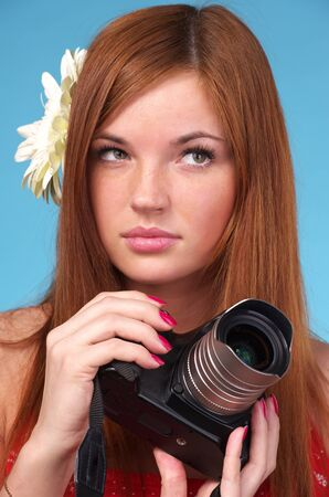 Young photographer woman holding camera against blue background Stock Photo - 12878382