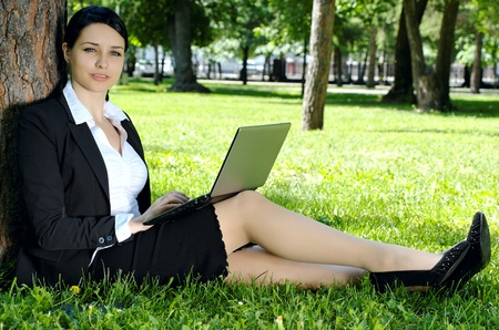 Business woman exploring internet using laptop in the park during rest