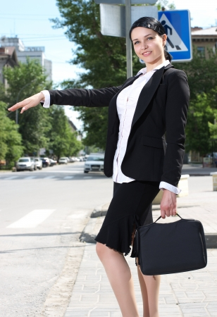 hailing: Beautiful youn business woman hailing taxi cab in the city Stock Photo
