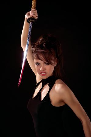 catfight: Beautiful woman in black dress with katana sword Stock Photo